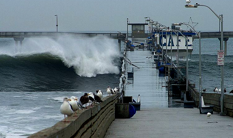 Waves crash over Ocean Beach Pier in 2002. Photo by Jon Sullivan via Wikipedia