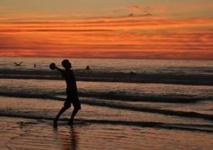 Boy tosses football at La Jolla Shores beach at sunset.  Photo by Chris Stone