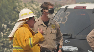 Firefighter consults with a sheriff's deputy as a blaze approaches.