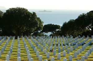 Gravestones at Fort Rosecrans National Cemetery with the USS Midway in the background. Navy photo