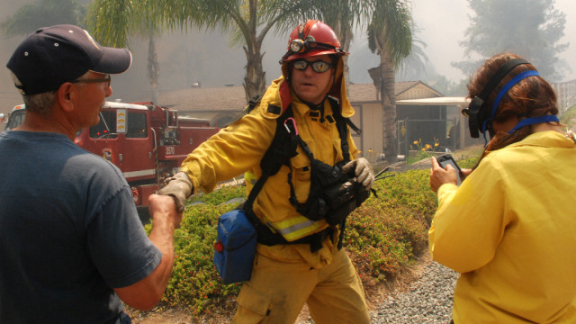 Award winner: Firefighter assures Al Said his team will do its best to save his home on Country Club Drive during San Marcos fires of May 2014. Photo by Chris Stone