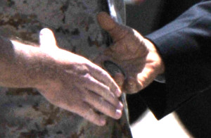 Closeup shows challenge coin in President Obama's hand just before handshake May 8, 2014, at Miramar air station. Photo by Chris Stone