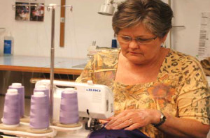 In 2010 photo, Kayla Park sews garments for roleplayers at Cubic Applications. Cubic supports the Joint Readiness Trianing Center with roleplayers, props and ephemera. Image via Fort Polk