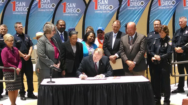 Mayor Kevin Faulconer signs the San Diego city budget while council members and city officials look on. Photo by Chris Jennewein