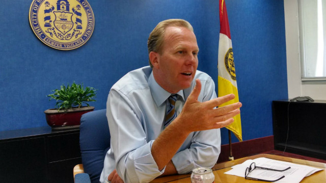 Mayor Kevin Faulconer with the city seal and flag in the background. Photo by Chris Jennewein