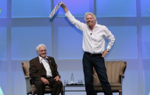 Sir Richard Branson displays part of Jim Greenwood's tie he snipped off after remarking that he had spent his life avoiding ties. Image via Flickr and BIO