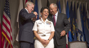 Secretary of the Navy Ray Mabus, left, and Wayne Cowles, husband of Adm. Michelle Howard, put four-star shoulder boards on Howard's service white uniform during her promotion ceremony at the Women in Military Service for America Memorial. U.S. Navy photo by Chief Mass Communication Specialist Peter D. Lawlor