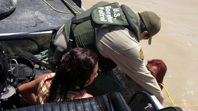 A Border Patrol agent rescues an immigrant woman and her daughter from the Rio Grande River during the border surge. Border Patrol photo