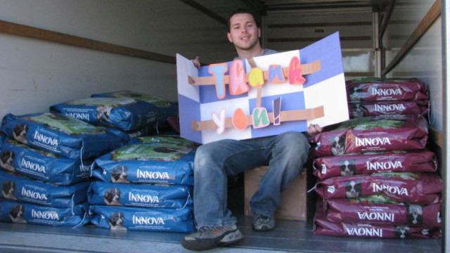 A San Diego PAWS volunteer  with donated dog food. Photo courtesy San Diego PAWS