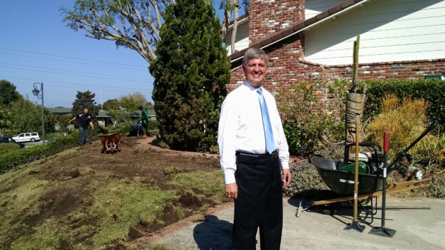 Dave Roberts outside his home as workmen remove his lawn. Photo by Chris Jennewein