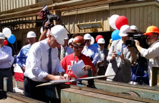 San Diego Mayor Kevin Faulconer signs paperwork after cutting the first piece of steel. Photo by Chris Jennewein