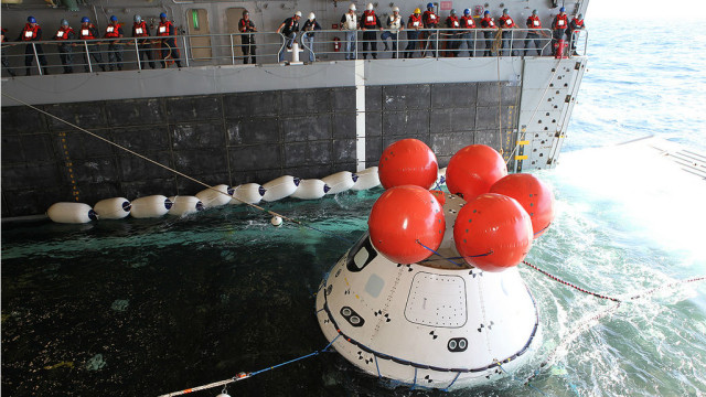 Sailors watch as the Orion is towed into the Anchorage's well deck on Wednesday. NASA photo