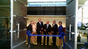 Denny Sanford, third from right, with Mayor Kevin Faulconer at the ribbon cutting for the center. Photo by Chris Jennewein