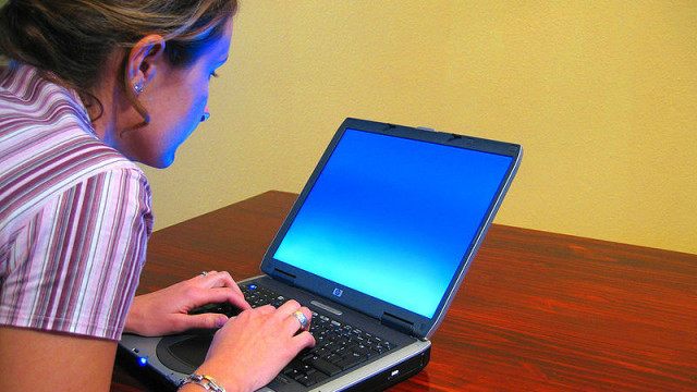 A woman typing on a laptop. Photo by Matthew Bowden via Wikimedia Commons