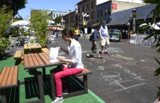 A woman pauses for lunch outside a Fourth Avenue downtown business while others check out the chalk drawings.