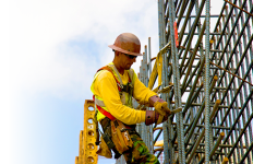Steel worker attaching a safety cable. Photo courtesy of OSHA.gov