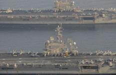 The aircraft carrier USS Carl Vinson (CVN 70), bottom, relieves the USS George H.W. Bush (CVN 77) in the Arabian Gulf. Navy photo