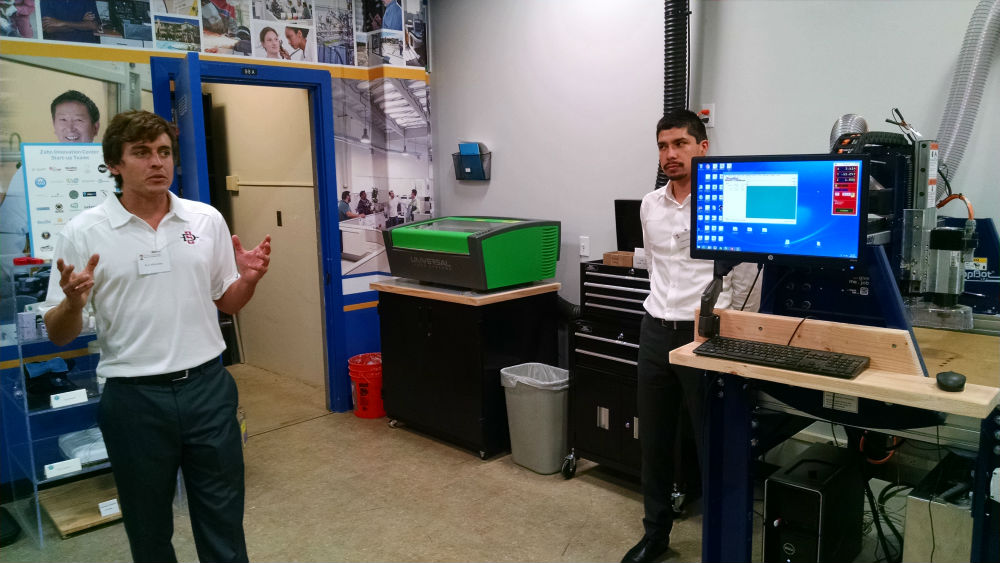 Kyle Kitzmiller (left) and Omar Miyazaki with a laser cutter and CNC router. Photo by Chris Jennewein