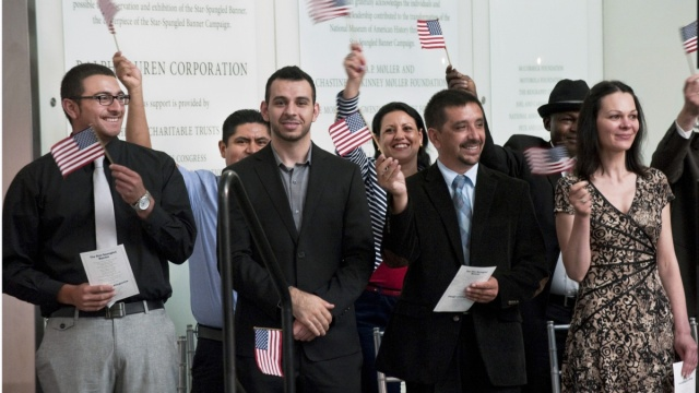 Candidates for citizenship wave American flags during a naturalization ceremony. Courtesy Department of Homeland Security