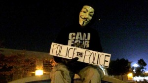 A protestor with a mask calls for more police evaluations.
