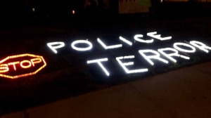 Protestors carried and laid out signs in the park demonstrating against police actions.