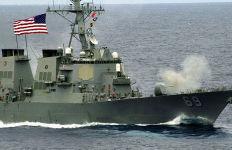 The Arleigh Burke-class, Aegis guided-missile destroyer USS Milius firing a deck gun. Navy photo