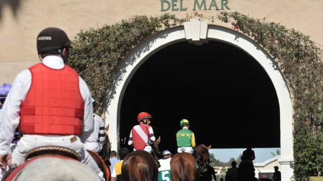 Horses and jockeys head for the track.