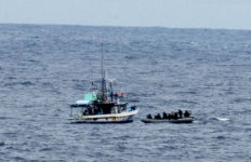 Navy and Coast Guard personnel approach the fishing boat, which was found to be smuggling cocaine. Navy photo