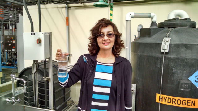 Halla Razak, director of public utilities, with pure recycled water. Photo by Chris Jennewein