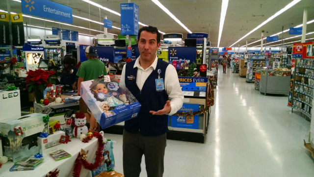 "Walmart spokesman John Forrest Ales holds a Disney ""Frozen"" Snow Glow Elsa Doll, one of the products on sale Thanksgiving Day. Photo by Chris Jennewein"