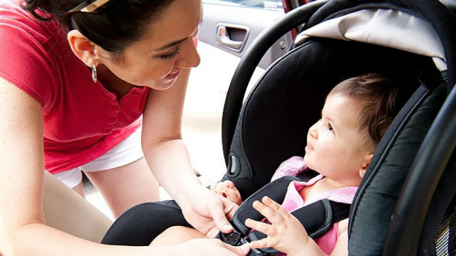 A woman checks a child in a car safety seat. Photo courtesy County News Center