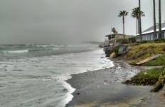 Waves cover the beach at high tide in Del Mar near Powerhouse Park. Photo by Chris Jennewein