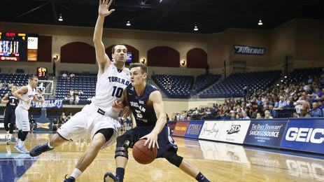 USD junior guard Duda Sanadze guards a BYU player. Courtesy of desertnews.com