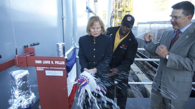 Martha Puller Downs breaks the bottle of champagne against the ship's hull. Courtesy NASSCO