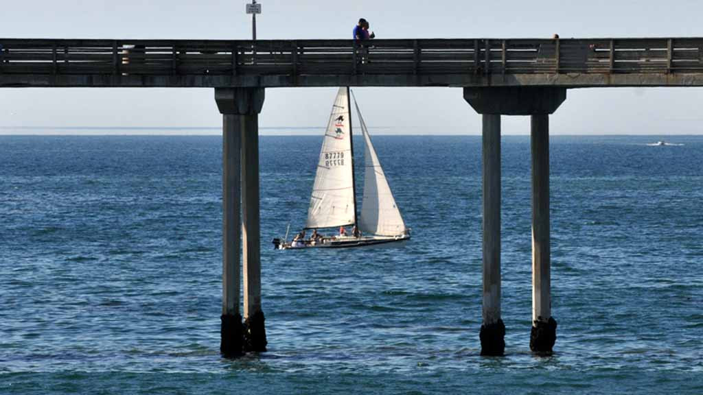 A couple strolls on the Ocean Beach Pier as others sail in warm weather. Photo by Chris Stone