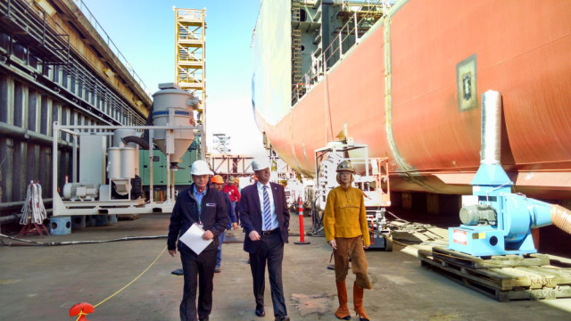 Dennis DuBard (left), Kevin Faulconer and Katherine Faulconer walk along the Lone Star State in its dry dock.