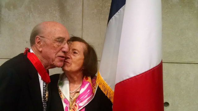 Dr. Roger Guillemin receives a kiss from his wife, Luciene, after receiving the award. Photo by Chris Jennewein