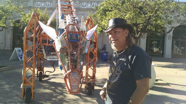 "Lindsay Lawlor with ""Russell,"" his electric giraffe, outside the Fleet Science Center. Photo by Chris Jenneein"