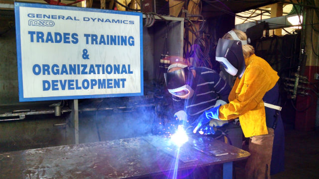 Katherine Faulconer practices welding before the keel laying ceremony. Photo by Chris Jennewein