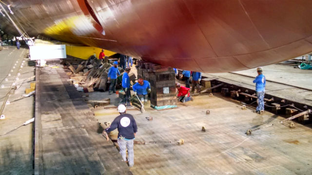 NASSCO workers cut away giant wooden blocks holding the bow of the ship. Photo by Chris Jennewein