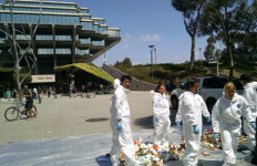 Students and administrators in hazmat suits collect trash outside the Geisel Library. Photo by Chris Jennewein