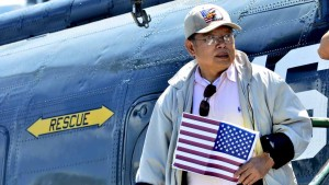 A visitor exits a helicopter similar to the ones used for evacuating refugees from Vietnam and the end of the war.