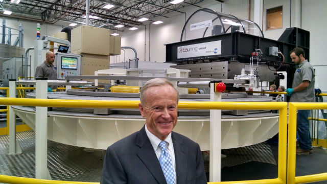 General Atomics Chairman and CEO Neal Blue in front of a machine winding the first magnet. Photo by Chris Jennewein