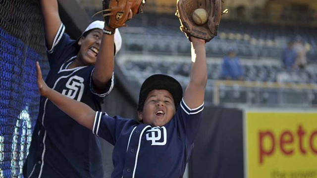 Young Padres fans practice catching a ball at the right field wall at Padre FanFest 2015.