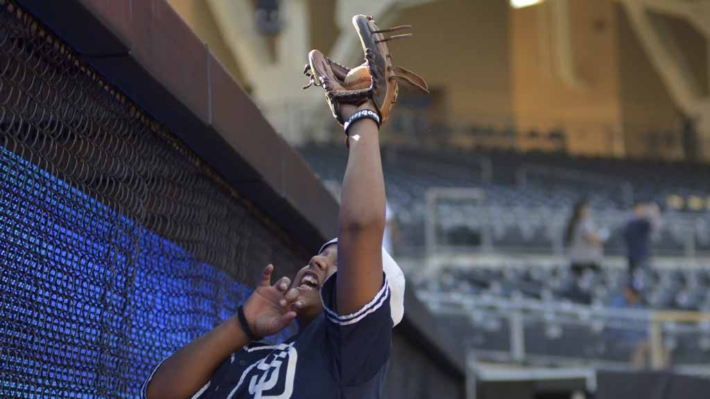 9e9055b66 A young fan makes a leap to catch a ball at the right field wall at Padres  FanFest 2015.