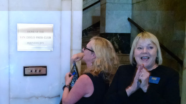 Press Club Executive Director Terry Williams claps while club President Kris Eitland unveils the plaque. Photo by Chris Jennewein