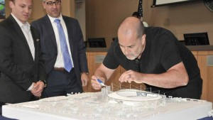 Dan Meis applies glue to his plastic model  of Chargers stadium for the Mission Valley site.