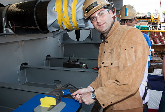 Eric Fabrikant hammers the initialed plate onto the ship's keel. Courtesy NASSCO