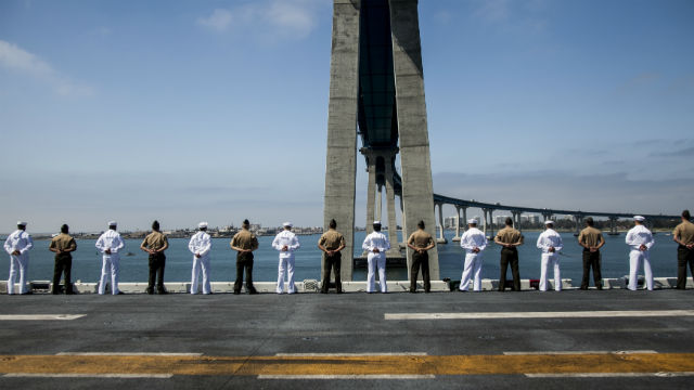 Marines and Sailors with man the rails aboard the USS Essex as it departs San Diego. Marine Corps photo by Cpl. Elize McKelvey