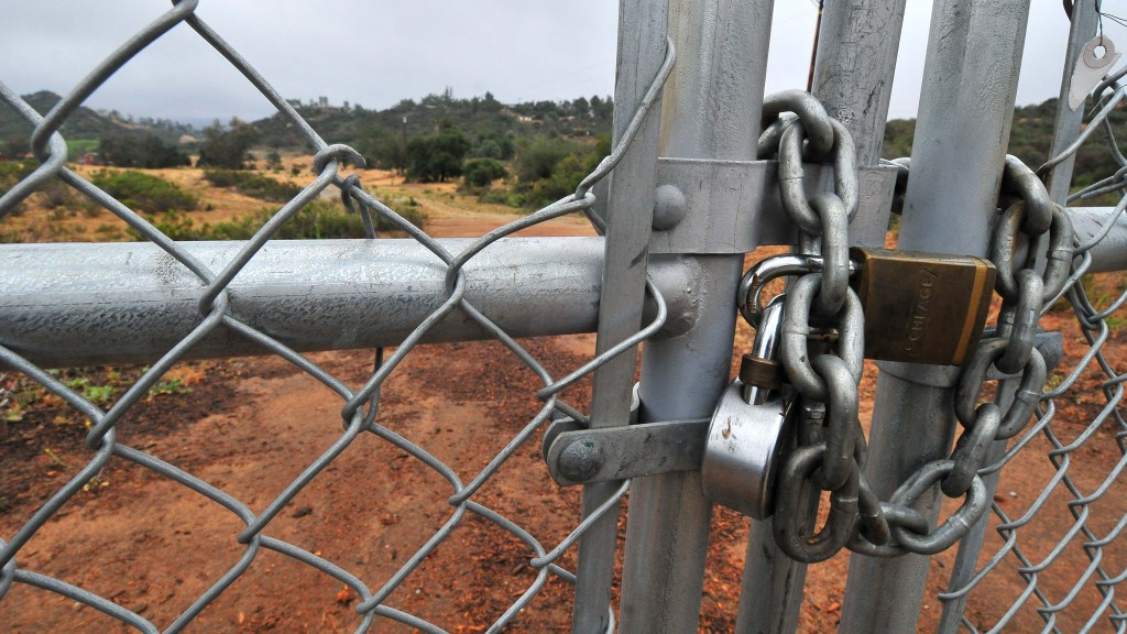 Locks are on fencing at the site of the proposed Alpine high school. Photo by Ken Stone